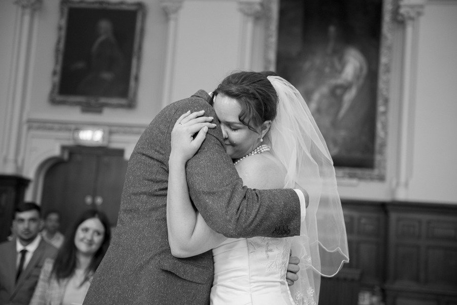 Bride and groom first kiss black and white