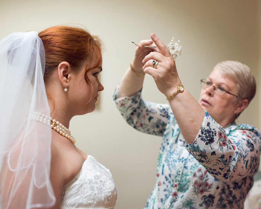Mother of the bride putting on veil