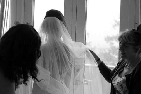 Mother of the bride putting veil on