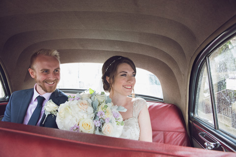 Bride and groom in car driving around st ives