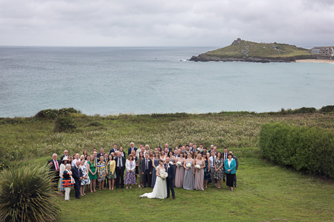 Group shot over porthmeor beach, st ives, and the island on the day they got married in St Ives