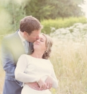 Bride and groom  kissing in a field at their wedding