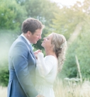 Bride and groom hugging at their country style wedding in a field
