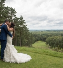 Bride and groom kissing over a field in cornwall