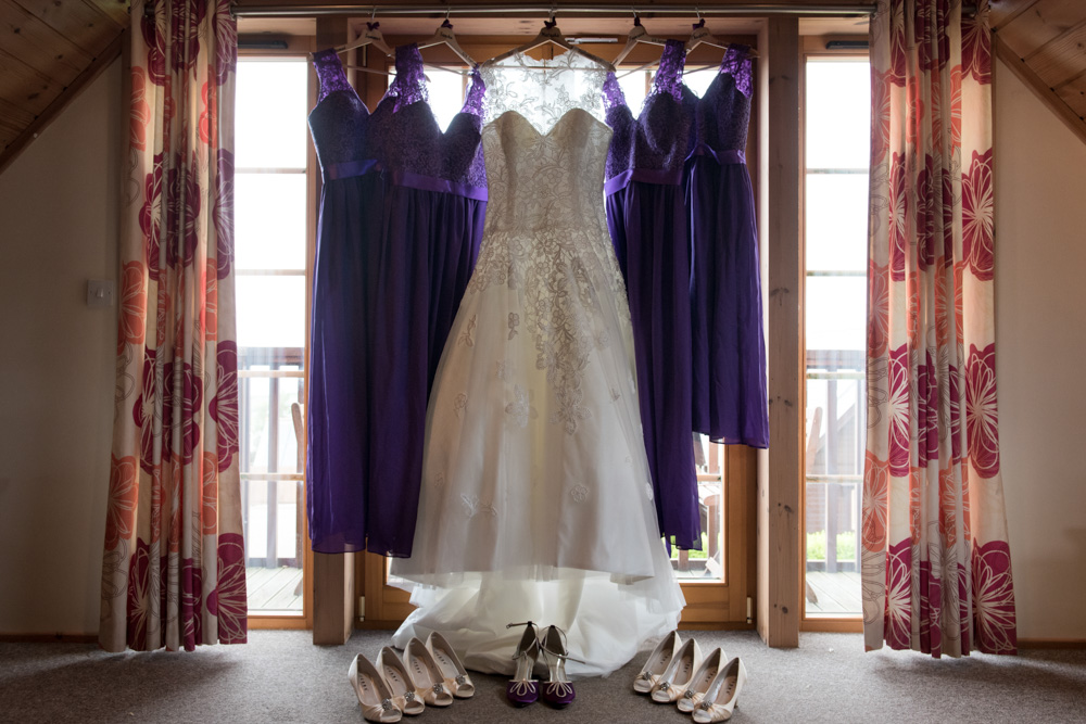 Brides dress hanging with bridesmaids