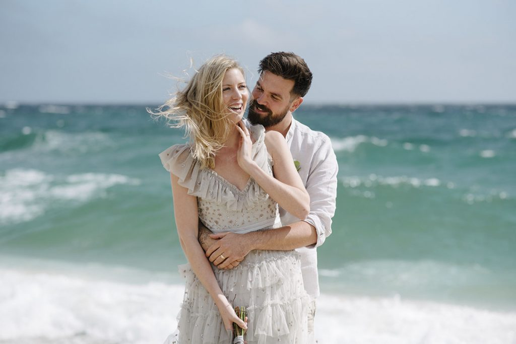 Relaxed casual bride and groom wearing a boho wedding dress laughing on Porth Curnow beach