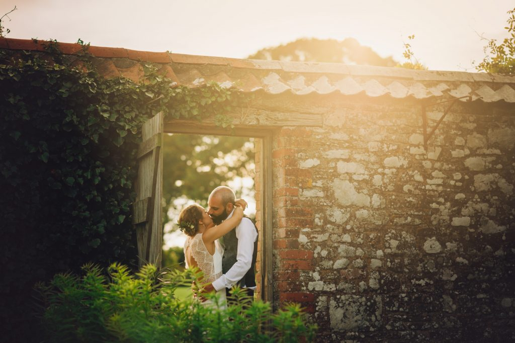 romantic intimate wedding during golden hour. Bride and groom stood in a doorway to an old barn with field of flowers