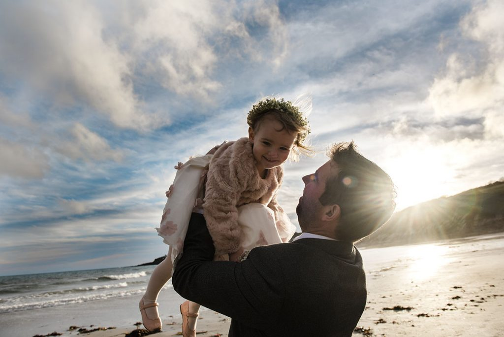 Dad and daughter playing on a beach in Cornwall, St ives. Wedding family photos
